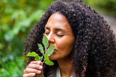 Mid adult woman with eyes closed smelling leaf in forest - p300m2250304 by Annika List