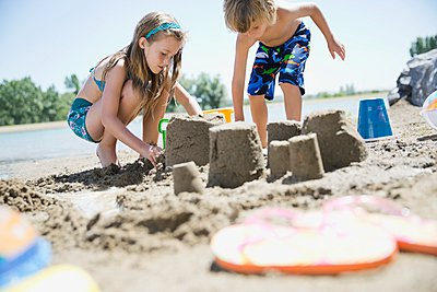 Siblings making sandcastles on the beach - p328m906390f by Hero Images