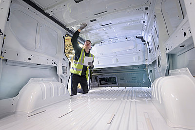 Apprentice vehicle inspector inspecting interior of vehicle in car factory - p429m1408221 by Monty Rakusen