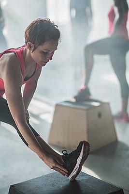 Athlete stretching leg in gym - p555m1411998 by John Fedele