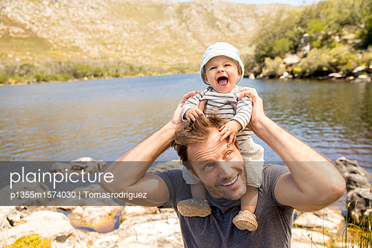 Father and baby on the lakefront - p1355m1574030 by Tomasrodriguez