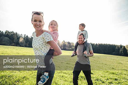 Happy family with two kids on a meadow in spring - p300m2166989 by Wilfried Feder