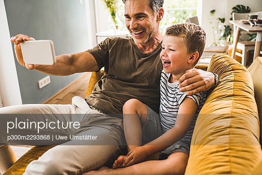 Father with arm around son while taking selfie through smart phone at home - p300m2293868 by Uwe Umstätter