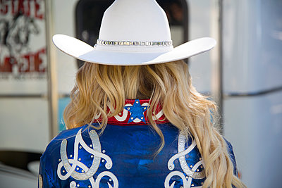 Rear view of woman with long blond hair wearing white Stetson hat and shiny blue jacket decorated with studs and white and red embroidery. - p1100m1570859 by Mint Images
