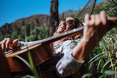 Woman with sunglasses laughing while playing guitar lying on a hammock - p1166m2171825 by Cavan Images