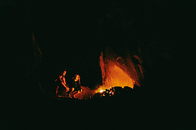 Young couple in front of camp fire at night in northern California. - p1166m2202081 by Cavan Images