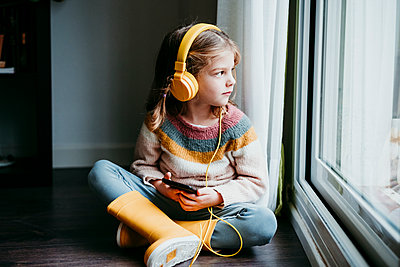 Girl wearing headphones using mobile phone while sitting by window at home - p300m2225337 by Eva Blanco