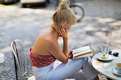 Young woman reading book in outdoor cafe - p312m2101676 by Pernille Tofte