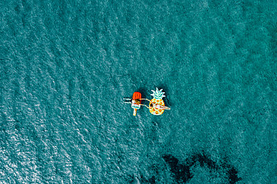 Two women on air mattress in the sea, drone photography - p713m2289241 by Florian Kresse