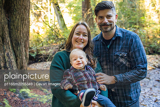 Portrait of Mother and father holding their young son outdoors. - p1166m2255349 by Cavan Images