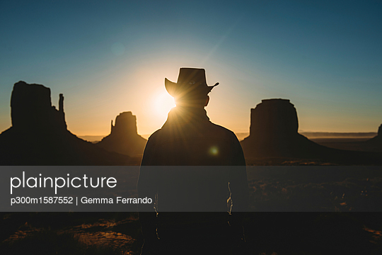 USA, Utah, Man with cowboy hat enjoying sunrise in Monument Valley - p300m1587552 von Gemma Ferrando