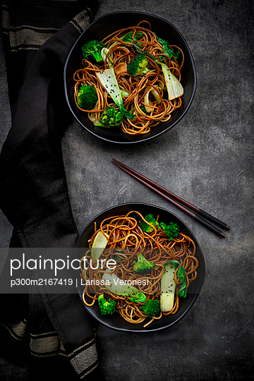 Overhead view of two bowls of soba noodles with pak choi and broccoli, soy sauce and black sesame - p300m2167419 by Larissa Veronesi