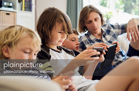 Father looking at boys playing games on smart phones and digital tablet in living room - p300m2202979 by Phillip Waterman