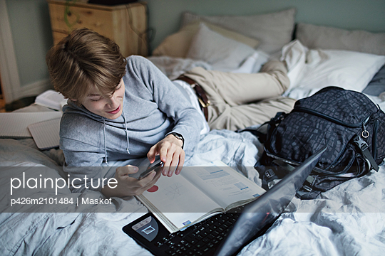 Addictive teenage boy using social media on mobile phone while doing homework in bedroom - p426m2101484 by Maskot