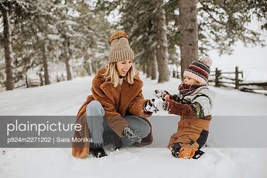 Canada, Ontario, Mother and daughter (2-3) playing in snow - p924m2271202 by Sara Monika
