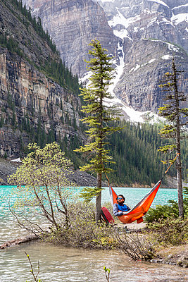 Man relaxing in hammock by Peyto lake at Icefields parkway - p1166m1519247 by Cavan Images