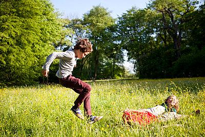 Kinder toben im hohen Gras im Park - p1195m1138150 von Kathrin Brunnhofer
