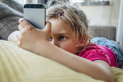 Girl lying on couch using smartphone - p300m1228338 by Joseffson