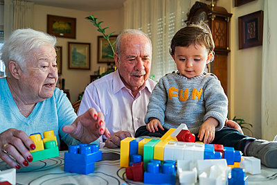 Great-grandparents and baby girl playing together with plastic building bricks at home - p300m1562993 by Gemma Ferrando