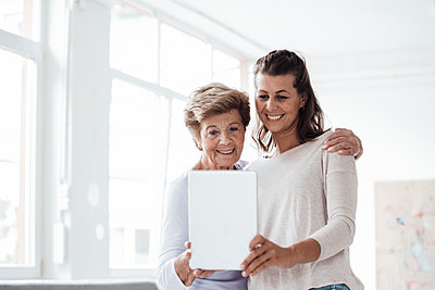 Smiling young woman with grandmother taking selfie through digital tablet at home - p300m2276856 by Gustafsson