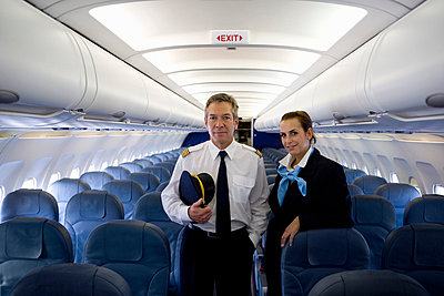 A pilot and a flight attendant standing in the cabin of a plane - p3018312f by Halfdark