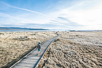 Clouds over boy walking alone on boardwalk across grass in front of Mono Lake, California, USA - p343m1490635 by Alasdair Turner / Aurora Photos