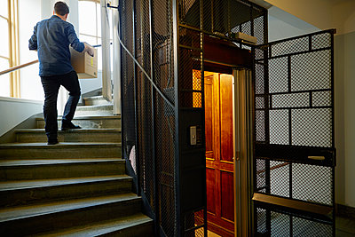 Sweden, Man walking on steps, carrying box - p352m1350188 by Folio Images
