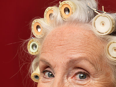 Close up studio portrait of senior woman in hair rollers - p429m895364f by Colin Hawkins