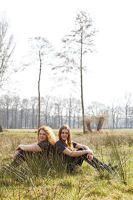 Freundinnen Rücken an Rücken - p606m1425982 von Iris Friedrich