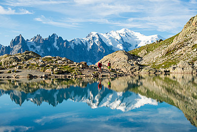 Hikers and the summit of Mont Blanc reflected in Lac Blanc on the Tour du Mont Blanc trekking route in the French Alps, Haute Savoie, Auvergne-Rhone-Alpes, France - p871m2068855 by Alex Treadway