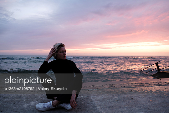Woman sitting near sea - p1363m2108792 by Valery Skurydin