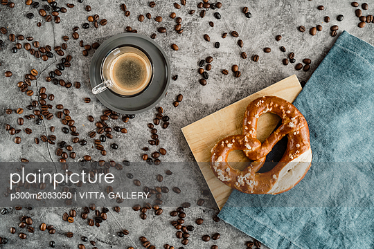 Cup of black coffee, coffee beans and pretzel on napkin and wooden board - p300m2083050 by VITTA GALLERY
