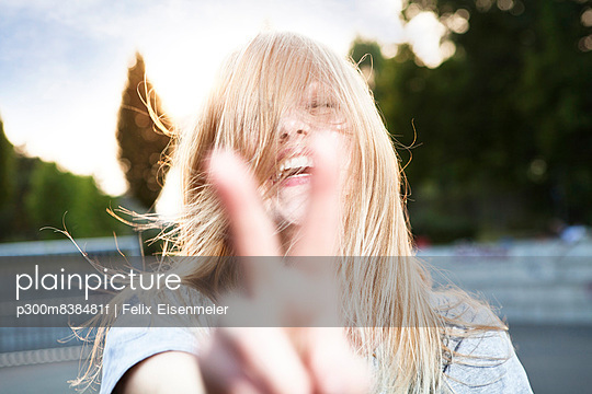 Young woman showing victory sign - p300m838481f by Felix Eisenmeier