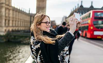 UK, London, young woman taking a selfie on Westminster Bridge - p300m1188871 by Marco Govel