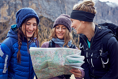 Three happy young women hiking in the mountains looking at map - p300m1563327 by Philipp Nemenz