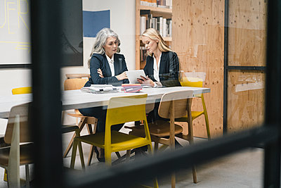 Mature and young businesswoman using tablet in loft office - p300m2170223 by Gustafsson