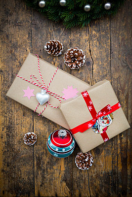 Wrapped Christmas presents, Christmas bauble and fir cones on dark wood - p300m977988f by Larissa Veronesi