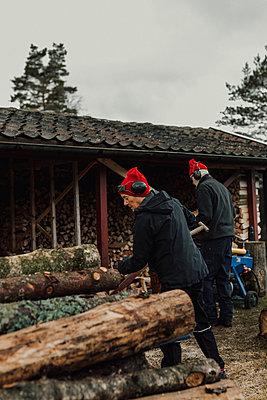 Senior man chopping wood - p312m2190966 by Jennifer Nilsson
