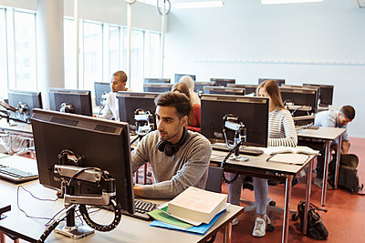 Male and female students using computers at library in university - p426m2072270 by Kentaroo Tryman
