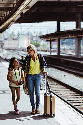 Full length of mother and daughter with luggage walking at railroad station - p426m2146019 by Maskot