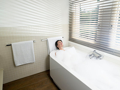 Woman in bathroom, taking a bath - p4295579 by Ghislain & Marie David de Lossy