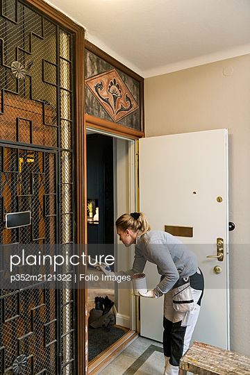 Painter painting door frame in apartment building - p352m2121322 by Folio Images