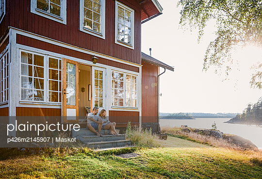 Full length of couple sitting at log cabin entrance by lake during summer - p426m2145907 by Maskot