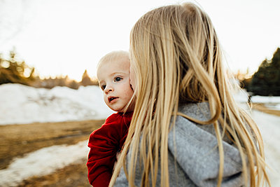 Girl kissing brother while standing on field during winter - p1166m1524593 by Cavan Images