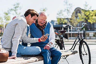 Senior man and adult grandson on a bench looking at cell phone - p300m1450027 by Uwe Umstätter