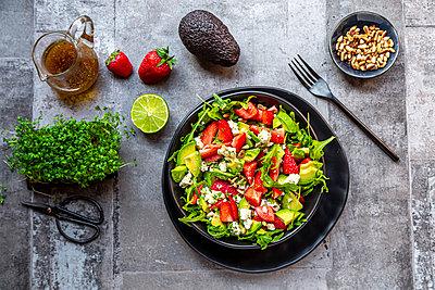 Strawberry avocado salad with feta, rocket, pine nuts and cress - p300m2103834 von Sandra Roesch