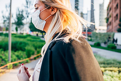 Close-up of businesswoman wearing mask walking in city - p300m2202908 by Eugenio Marongiu