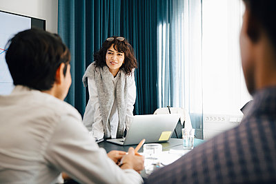Smiling businesswoman planning strategy with male colleagues in board room during meeting - p426m2195268 by Maskot
