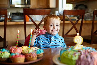 Caucasian boy admiring birthday cake - p555m1414420 by Jeff Greenough