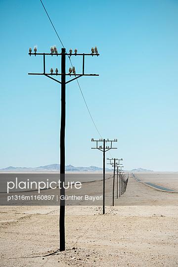 Strommasten bis zum Horizont in der Wüste vor Lüderitz, Namibia, Afrika - p1316m1160897 von Günther Bayerl